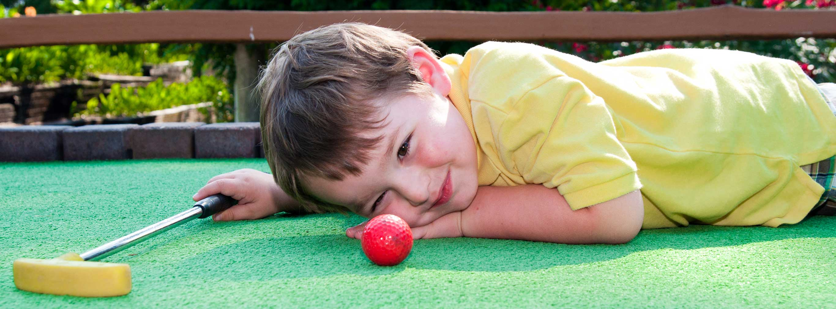 carnival amusements of s a child playing miniature golf
