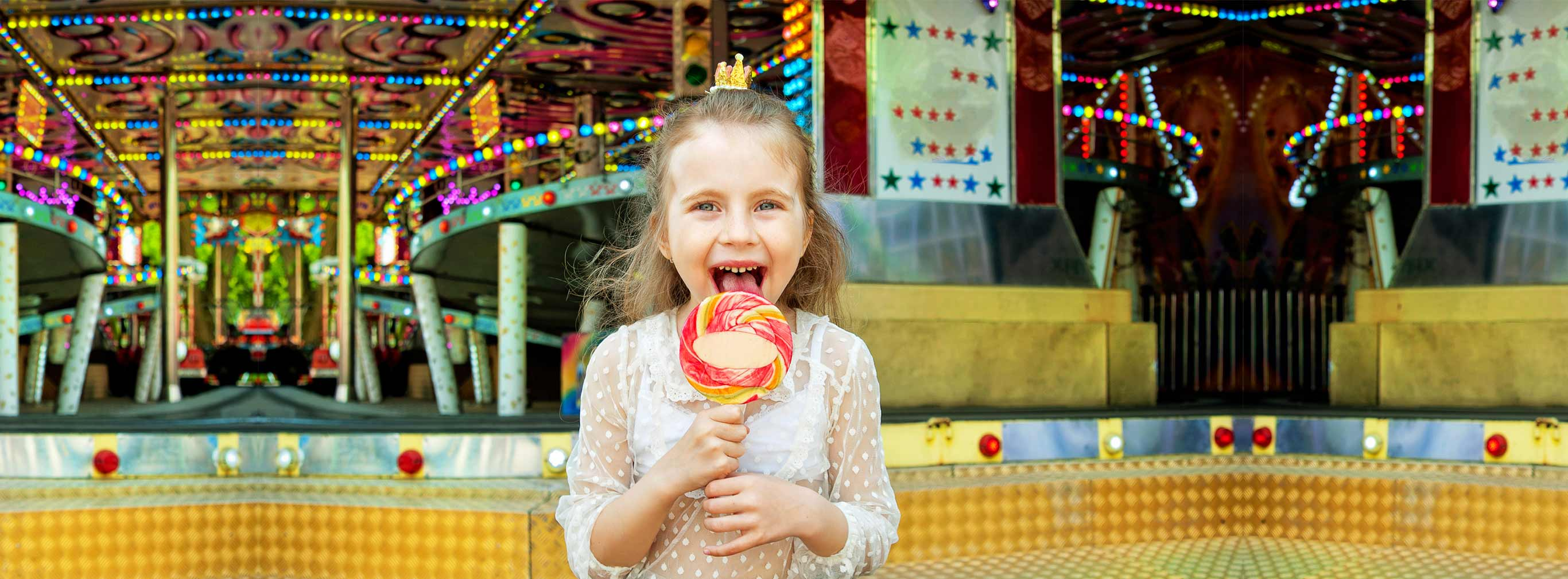 carnival amusements of s a cute little girl with lollipop at amusement park