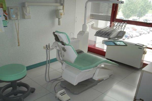 un sedile verde, uno sgabello e degli attrezzi dentistici