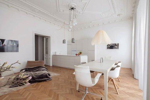 una cucina open space con dei lampadari moderni a sospensione
