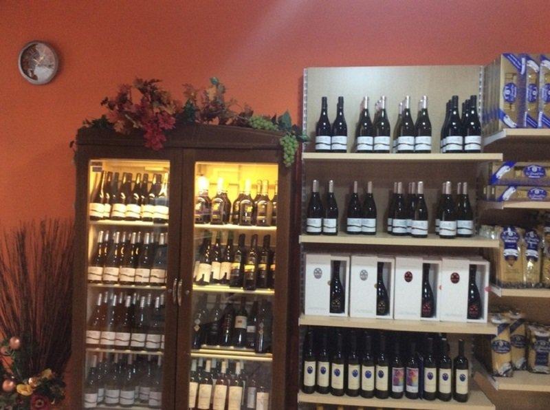 Angolo del business in cui vediamo pacchetti di pasta in un ripiano e diversi vini ,alcuni nella ripiano e altri in frigorifero