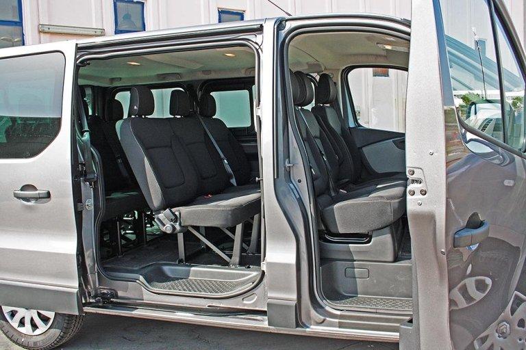 Minivan con le porte aperte, possiamo vedere le sedili di colore grigio