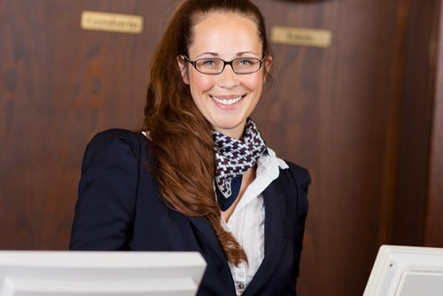 Receptionist at hotel lobby giving you a very warm welcome