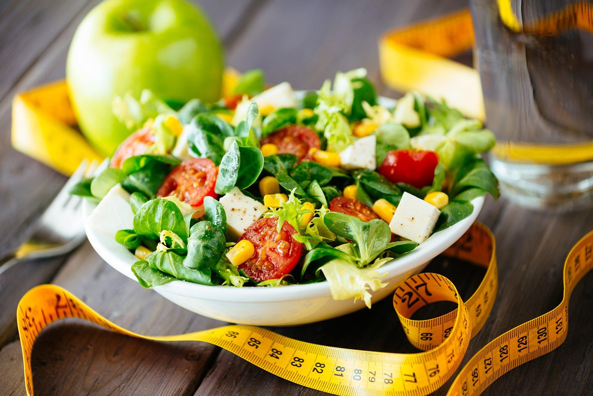 Una ciotola di insalata con mais, valeriana, pomodori, tofu, olio d'oliva e aromi e un metro di gomma di color giallo
