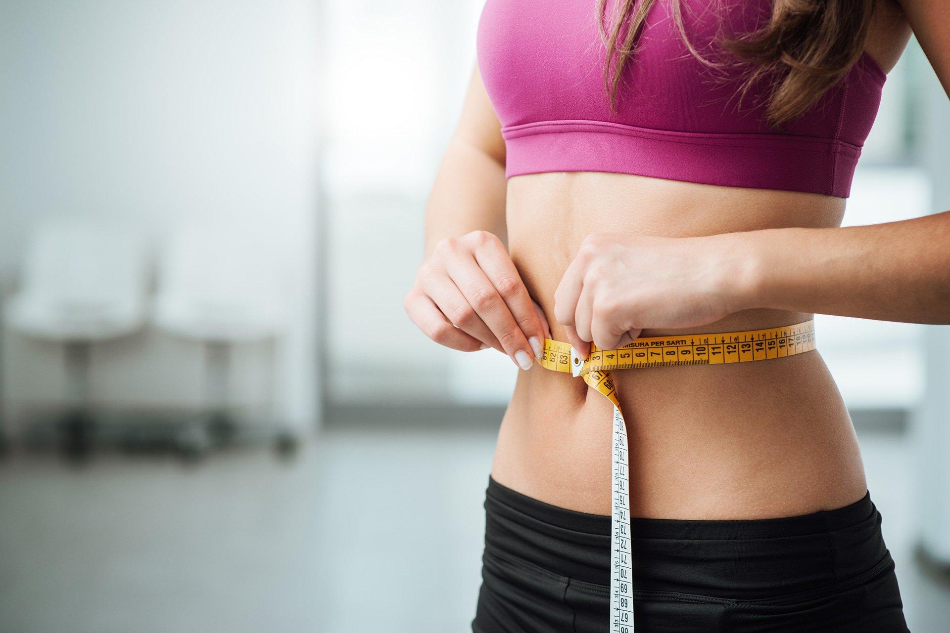 donna con top viola e pantaloncini neri si sta misurando la vita con un metro