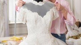 abito da sposa su manichino, sarta che lo aggiusta, laboratorio di sartoria