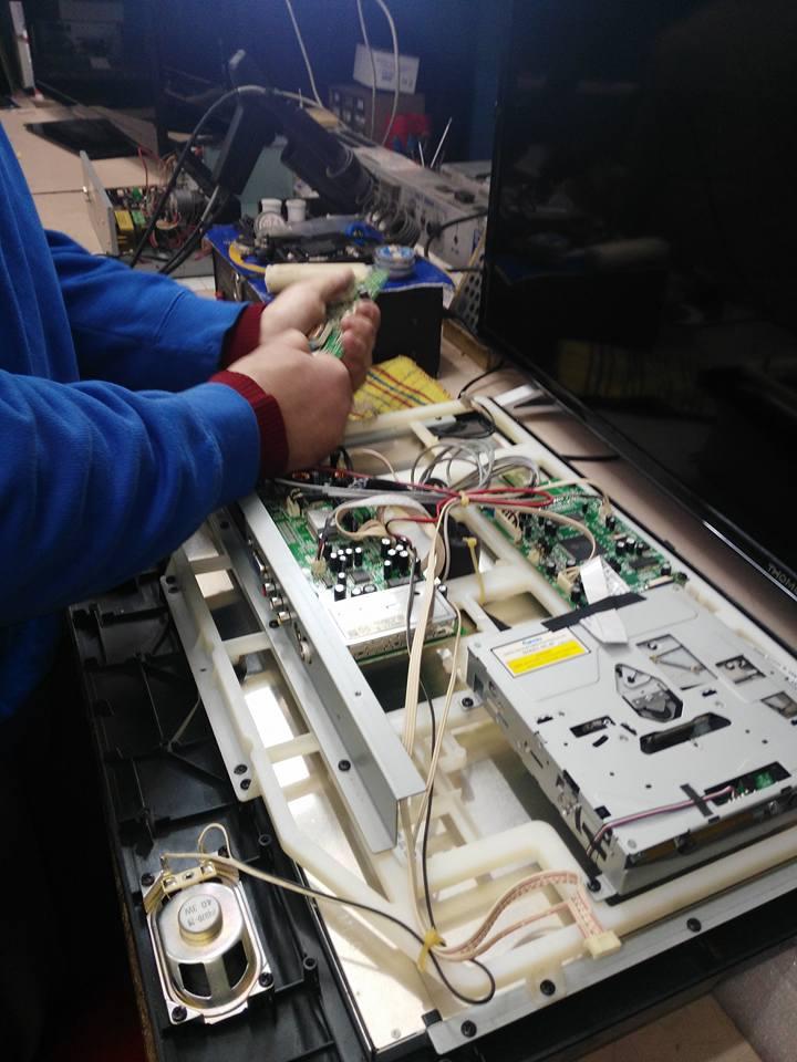due mani con in mano un componente elettronico verde e sotto una tv disassemblata