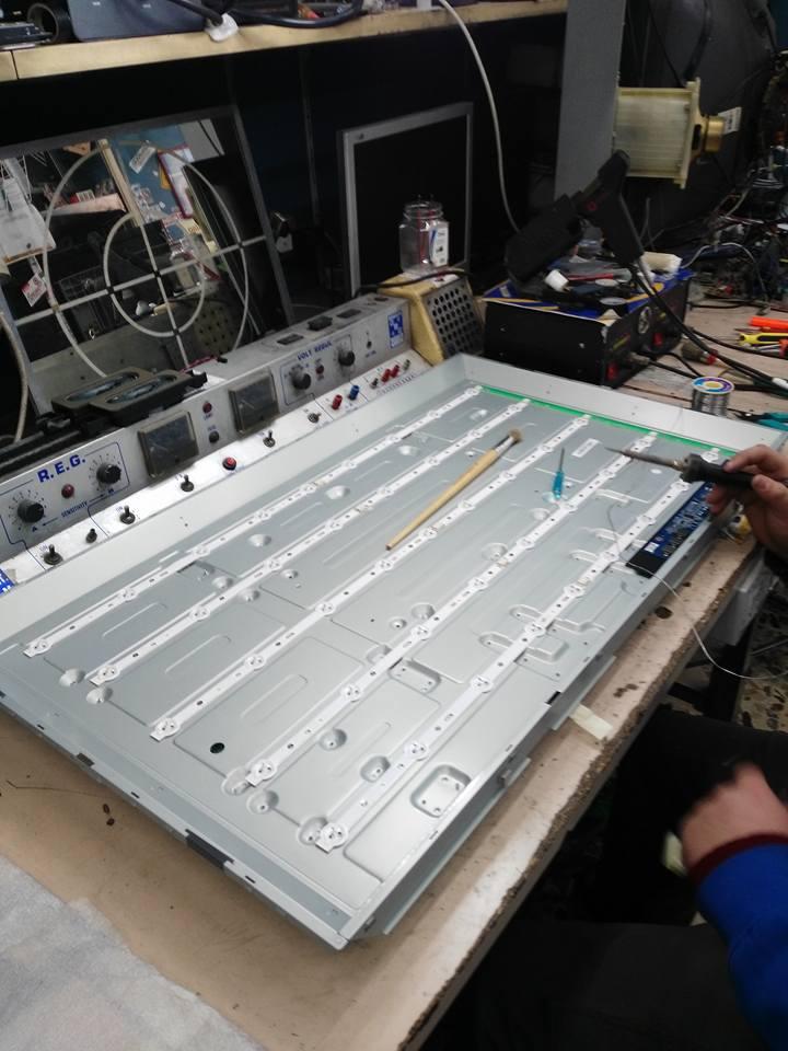 una tv disassemblata su un piano da lavoro e una mano con in mano un cacciavite