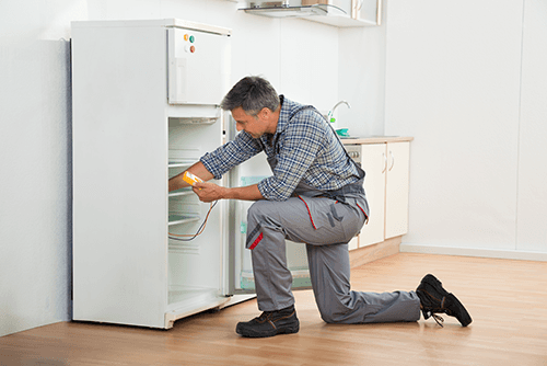 Experienced electrician repairing refrigerator