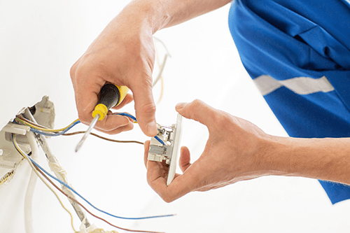 Experienced electrician fixing socket