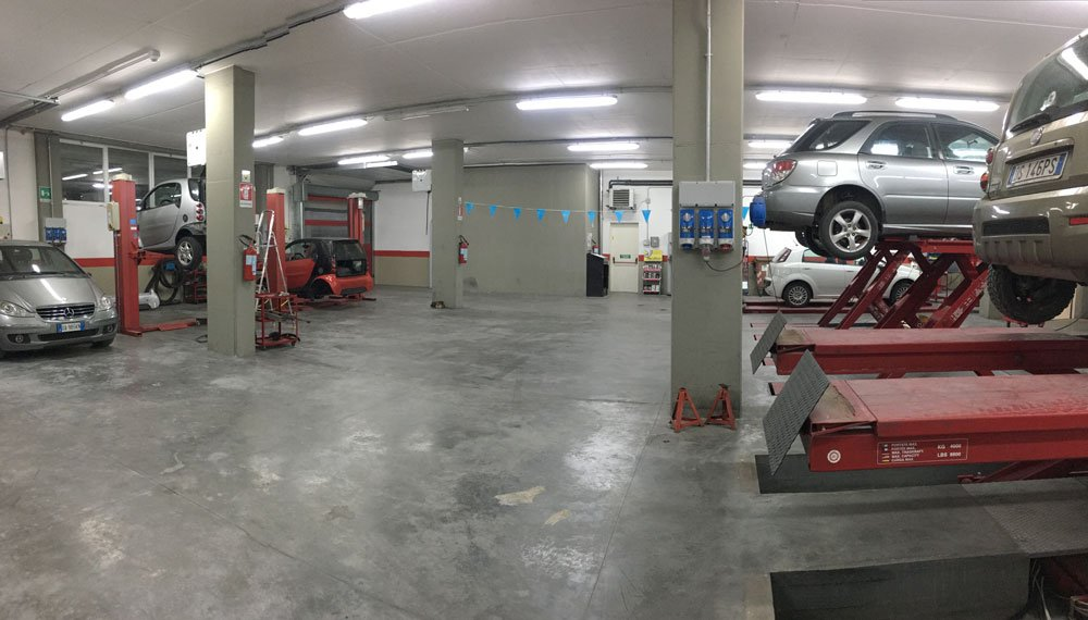 interno dell'officina con delle macchine sul ponte