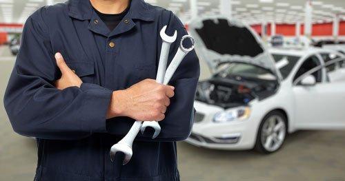 un meccanico con due chiavi inglesi in mano e dietro una macchina con il cofano aperto