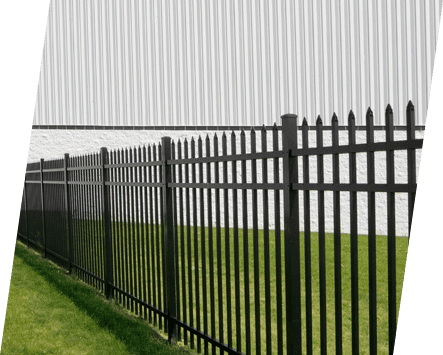 A black palisade fence in front of a white industrial building