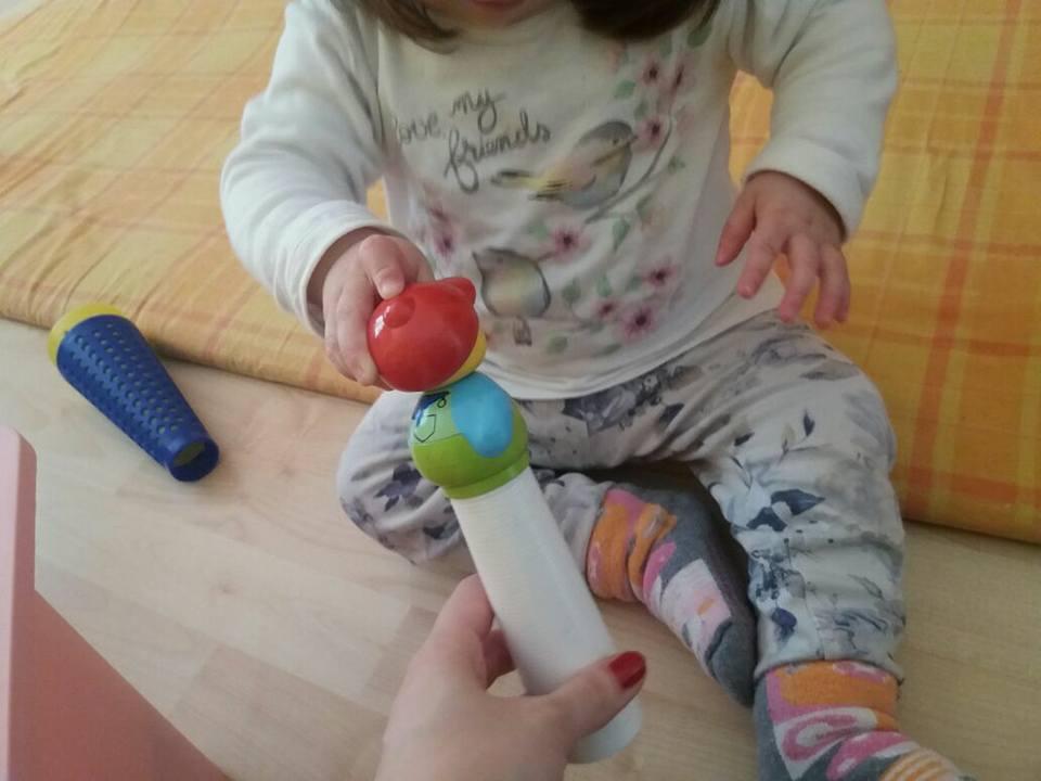 mano che porge un giocattolo a una bambina