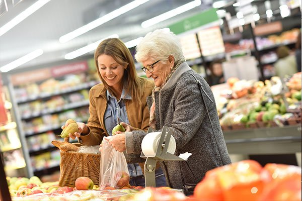 Una donna anziana mentre sorride e tiene le mani di una donna con un camice