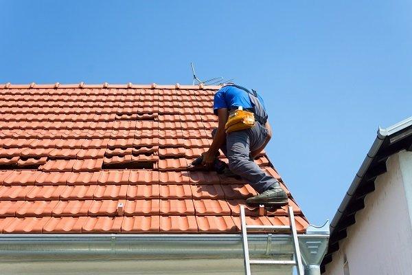 operatore sistemando piastrelle sul tetto