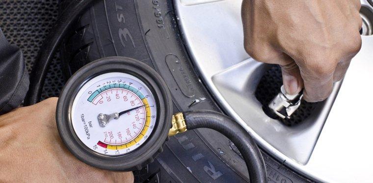 Mechanic checking tyre pressure