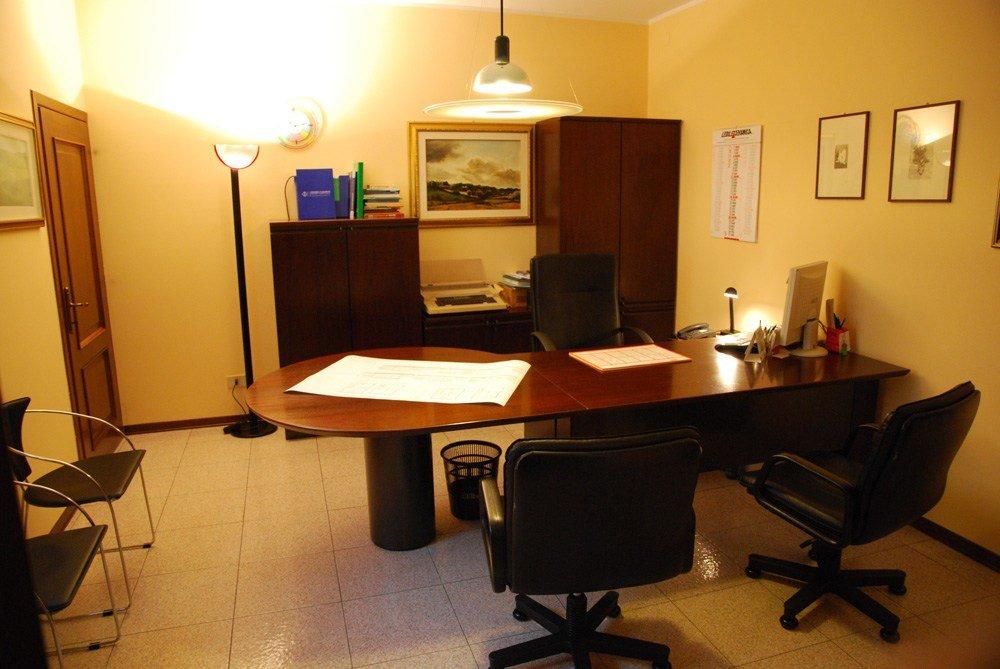 uno studio con una scrivania marrone e delle sedie