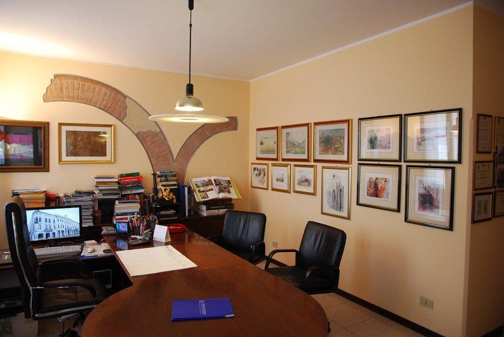 uno studio con una scrivania in legno e delle sedie