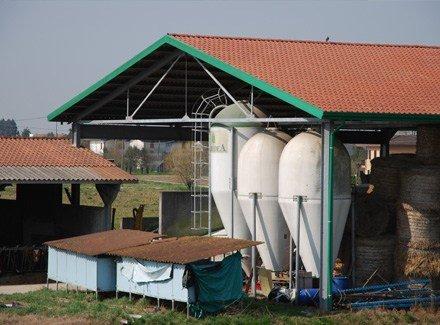 una fattoria con tre grosse taniche e delle balle di fieno