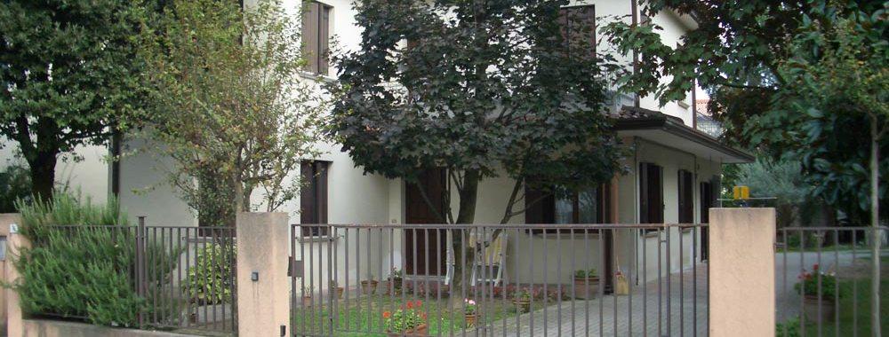 un cancello e vista degli alberi e di alcune case