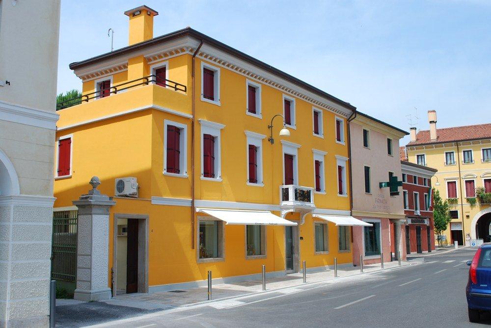 una casa arancione e altre accanto