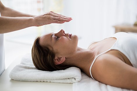 Cropped hands of therapist performing reiki on young woman at spa in Buena Vista