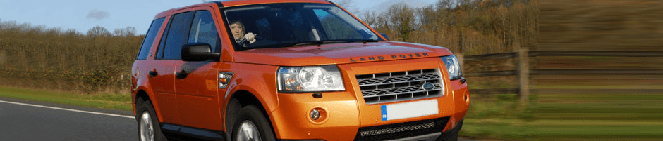 orange land rover driving on a road in maidenhead