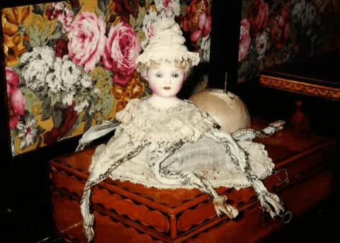una bambola sopra un portagioie in legno