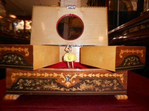 un carillon con degli scompartimenti e una bambola ballerina al centro