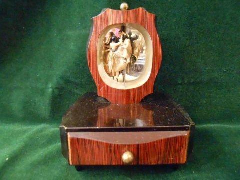 un carillon portagioie con una cornice con una foto sopra e un cassetto