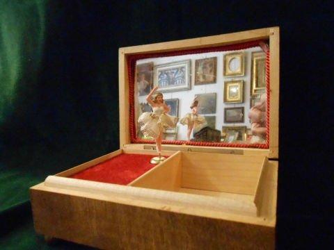 un carillon con uno specchio e una bambola ballerina al centro