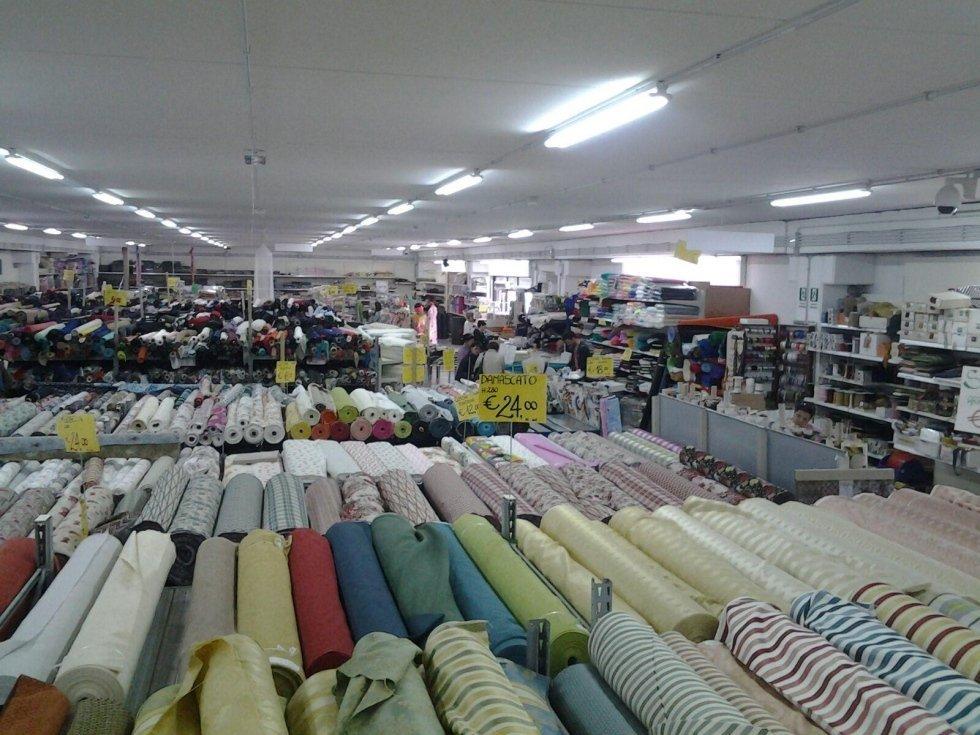 dei tessuti di diversi colori in esposizione in un negozio