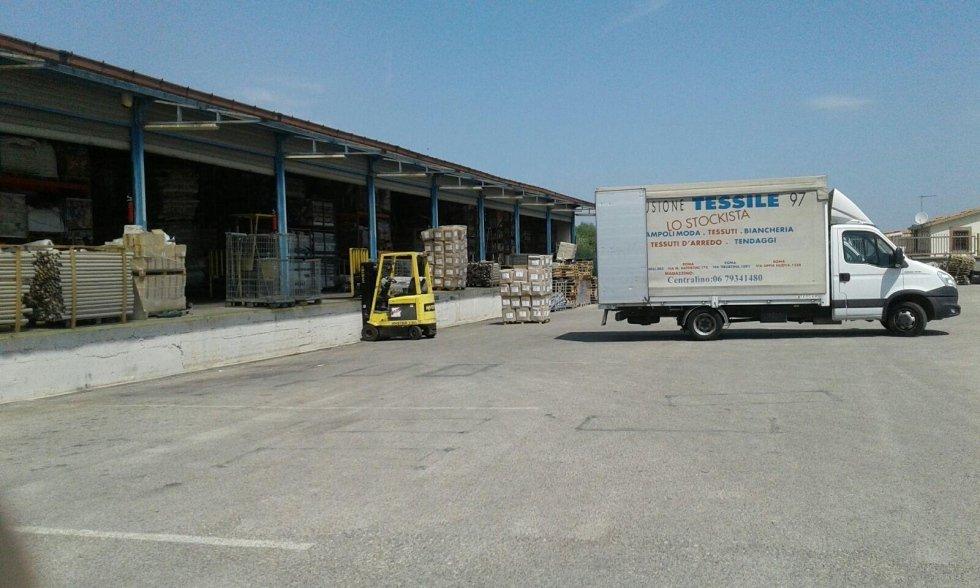 un camion bianco, un muletto e un magazzino sotto una copertura