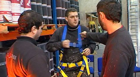 A roofer getting into his harness