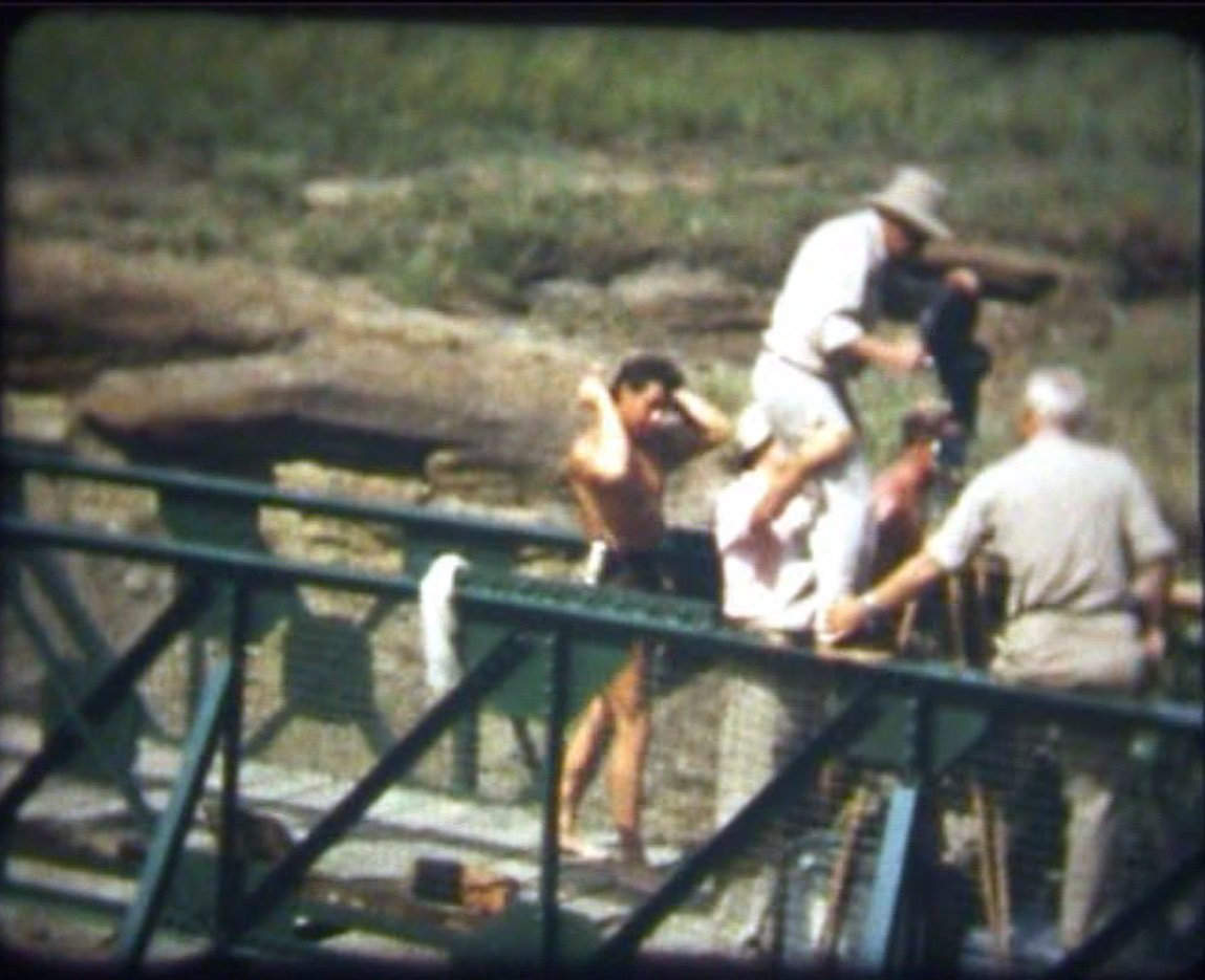 Gordon Scott combing his hair, while the crew prepares a scene on a bridge