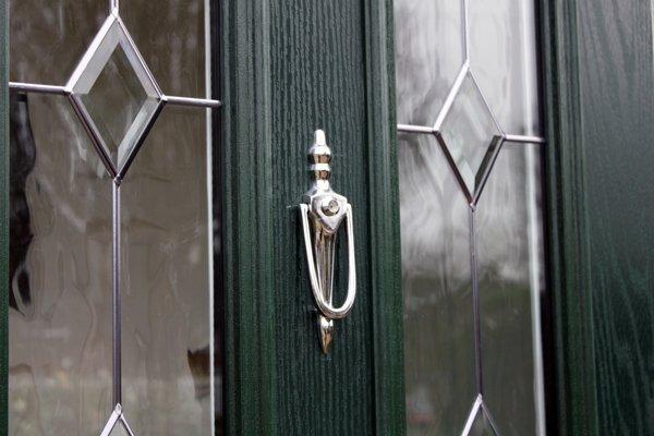 Close-up of knocker on green composite door