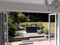 Two open bi-folding patio doors leading into a living room.