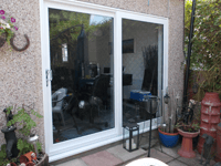 A white room with two large three pane sliding patio doors, leading onto a garden.
