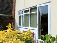 White uPVC door on a porch with casement windows.