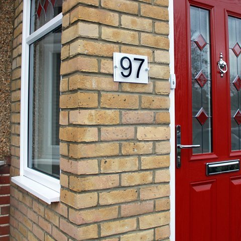 Close-up of porch with the number 97 on a brick wall