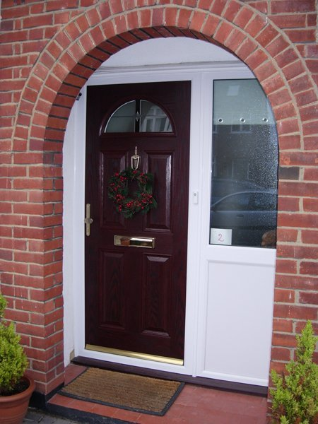 Mahogany entrance door with a Christmas wreath, surrounded by a red brick arch.