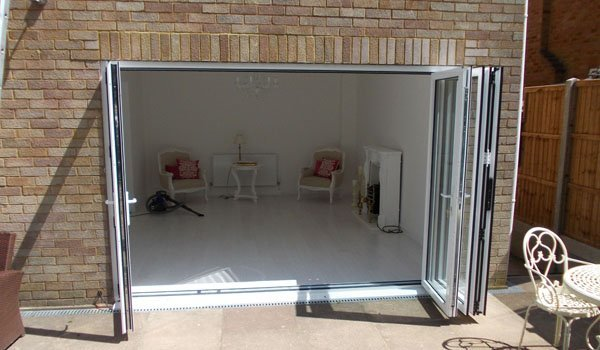 Looking into a white furnished living room through open sliding patio doors