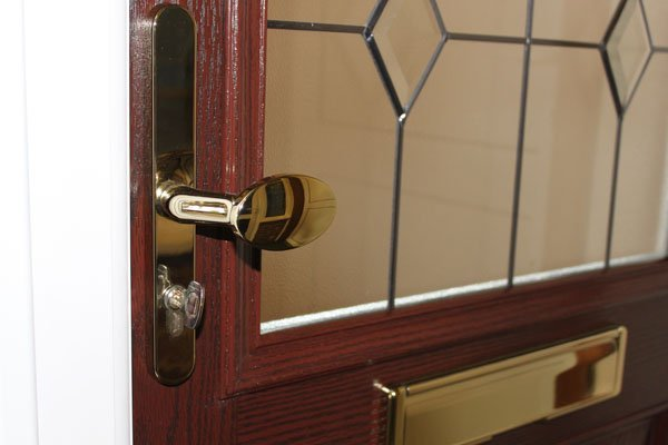 Close up of a mahogany door with a brass door handle and letter plate.