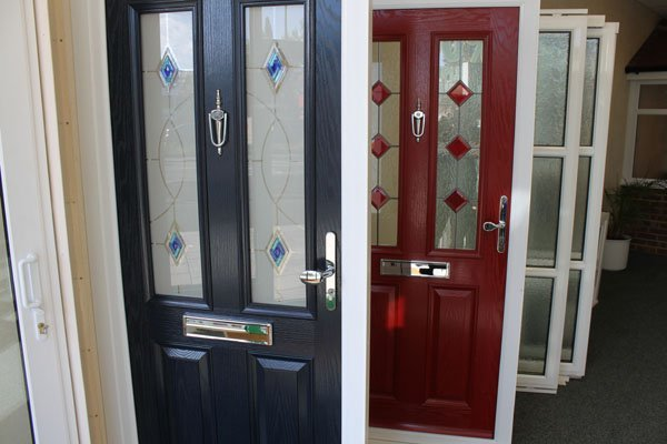 A red door and a blue door, both with stained glass window panels in the Window Centre showroom, Harrow.