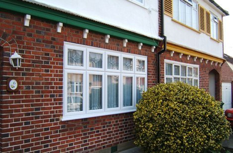 White flat casement windows on a house that is half red brick on the bottom and white cement on the top.