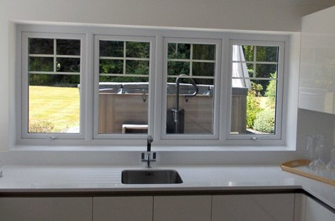 Inside a white kitchen with casement windows facing a garden with a hot tub.