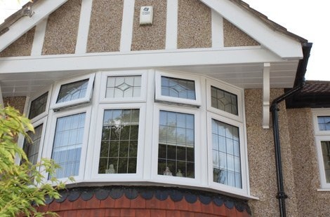Close up of Bay windows on the second storey of a house. Diamond shape pattern on the top of the window.