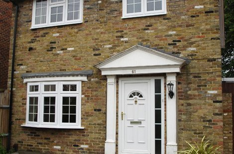 Rectangular bay windows featured on a house with a white door and white pointed arch.