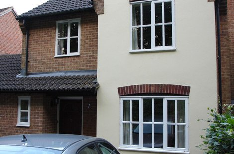 White sash windows on a house that is red brick on the left and cream cement on the right.